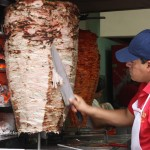 Slicing off grilled pork for tacos árabes in Puebla, Mexico
